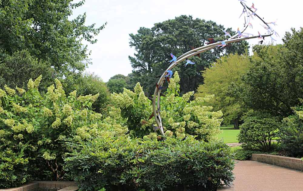 Sculpture of birds in flight in a botanical garden is used as an arch to connect visitors from one area to another..