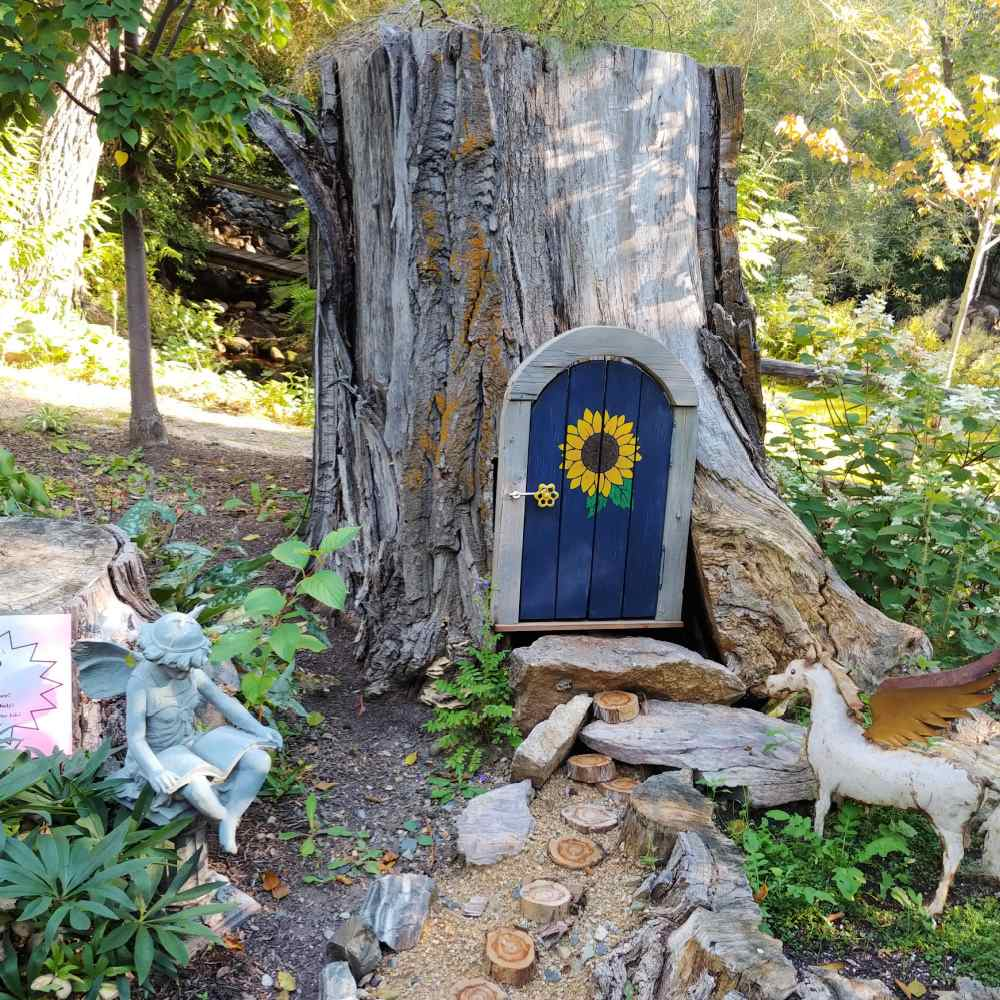 Tree stump with a small door cut into it and unicorn nearby.