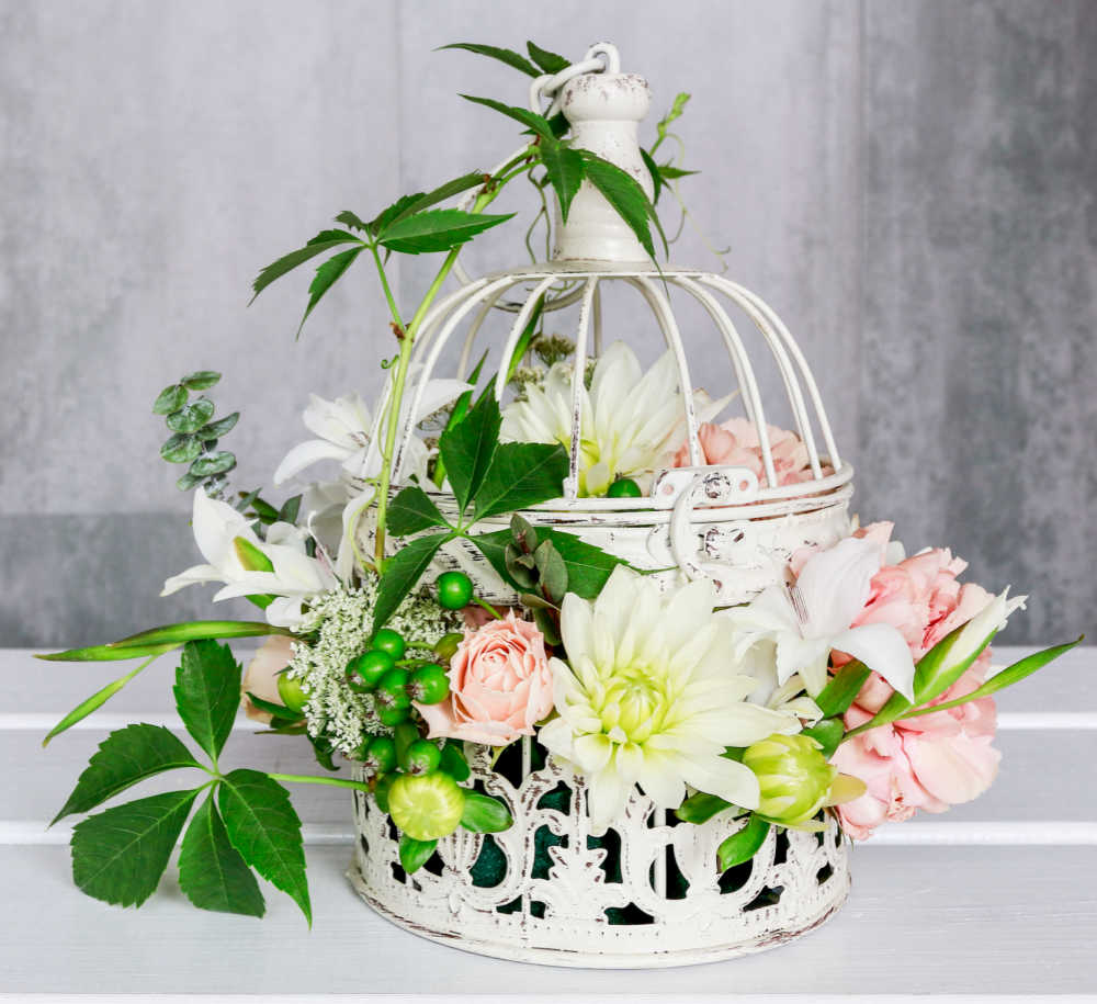 Pretty white bird cage with silk flowers and leaves.