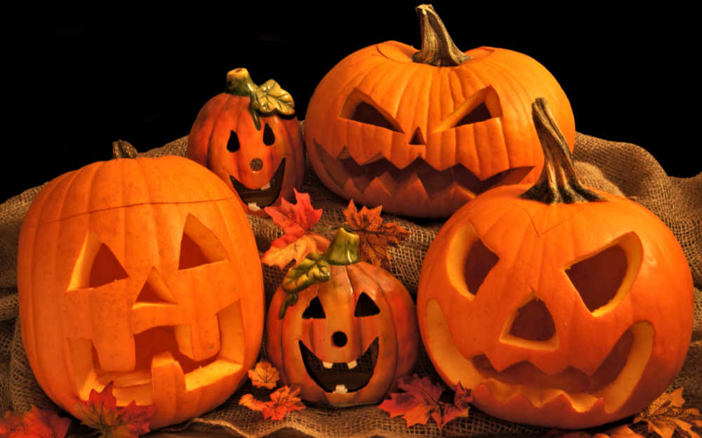 Stack of carved pumpkins with leaves.