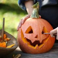 Man carving a pumpkin and pumpkin guts